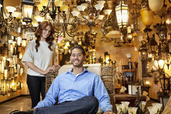 Portrait of handsome young man sitting while woman standing background in lights store Royalty Free Stock Photography