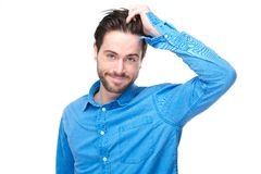 Portrait of a handsome young man smiling with hand in hair. Close up portrait of a handsome young man smiling with hand in hair Royalty Free Stock Photos