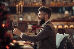 Portrait of handsome young man smiling and holding glass of red wine over blurry background.  royalty free stock photography