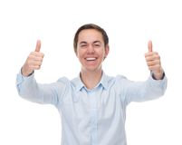 Portrait of a handsome young man smiling with thumbs up in celebration Stock Images