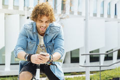 Portrait of Handsome young man smiling when he is using his mobi Stock Photography