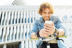 Portrait of Handsome young man smiling when he is using his mobi Royalty Free Stock Photography