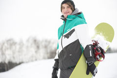 Portrait of handsome young man with snowboard in snow Stock Photos