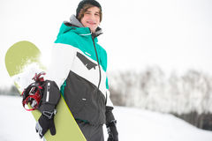 Portrait of handsome young man with snowboard in snow Royalty Free Stock Photo