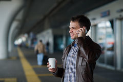 Portrait of a handsome young man stand near the airport waiting for next flight and talking on mobile phone royalty free stock photo