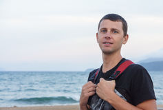 Portrait of handsome young man standing against a beach Stock Image