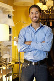 Portrait of a handsome young man standing with arms crossed in lights store Royalty Free Stock Photo