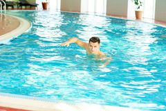 Young Man Swimming in Pool. Portrait of handsome young man swimming in indoor pool at health club, looking at camera, copy space Royalty Free Stock Photo