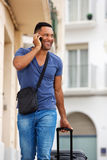Handsome young man talking on mobile phone with bag. Portrait of handsome young man talking on mobile phone with bag Royalty Free Stock Photo