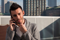 Portrait of a handsome young man talking on phone Stock Images