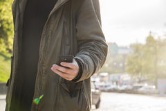 Portrait of handsome young man using his mobile phone in the street. Portrait of handsome young man using his mobile phone in the street in sanly day Royalty Free Stock Image