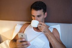 Portrait of handsome young man using a mobile phone and drinking. Cup of coffee in the white bed Stock Image