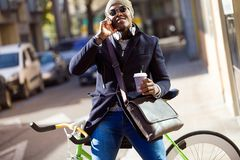 Handsome young man using mobile phone and fixed gear bicycle in the street. Portrait of handsome young man using mobile phone and fixed gear bicycle in the Royalty Free Stock Photography