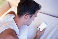 Portrait of handsome young man using a mobile phone and messagin. G in the white bed Royalty Free Stock Images