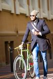 Handsome young man walking with his bike in the street. Portrait of handsome young man walking with his bike in the street Stock Images