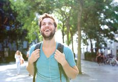 Portrait of a handsome young man walking outdoors with backpack. Close up portrait of a handsome young man walking outdoors with backpack Royalty Free Stock Image