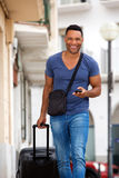 Handsome young man walking with suitcase and mobile phone. Portrait of handsome young man walking with suitcase and mobile phone Stock Photo
