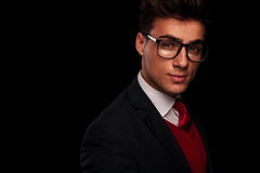 Portrait of handsome young man wearing glasses. Close portrait of handsome young man wearing glasses, looking at the camera while smiling in dark studio Stock Photography