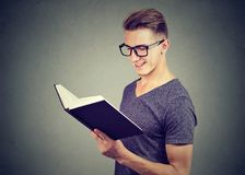 Portrait handsome young man wearing glasses reading a book Royalty Free Stock Photo