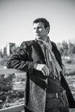 Portrait of handsome young man wearing jeans, coat and scarf Royalty Free Stock Image