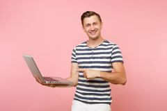 Portrait of handsome young man wearing striped t-shirt working on laptop computer, copy space isolated on trending royalty free stock photo