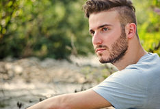 Portrait of handsome young man in white t-shirt in nature. Portrait of handsome young man in white t-shirt outdoors, looking to a side royalty free stock image