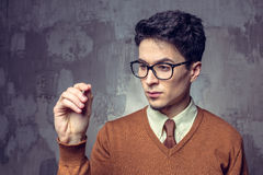 Portrait of a handsome young man writting something on a glass writeboard. Portrait of a handsome young man wearing glasses and writting something on a glass Royalty Free Stock Image