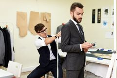 Tailor Fitting Handsome Businessman for Bespoke Suit. Portrait of handsome young men being fitted in bespoke suit by tailor in traditional atelier studio Royalty Free Stock Images