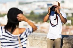 Handsome young man taking photo of his girlfriend in the street. Royalty Free Stock Photos
