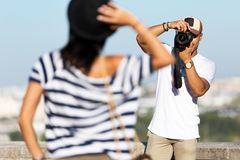 Handsome young man taking photo of his girlfriend in the street. Royalty Free Stock Images