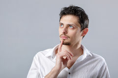 Portrait of handsome young pensive man in white shirt on gray ba Royalty Free Stock Photography