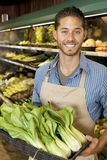 Portrait of handsome young sales clerk with bok choy in market Stock Images