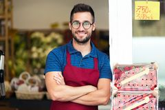 Handsome young salesman looking at camera in health grocery shop. Portrait of handsome young salesman looking at camera in health grocery shop stock images