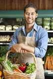 Portrait of handsome young salesperson standing with basket full of vegetables Stock Photography