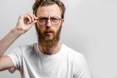 Portrait of handsome young serious man touching glasses stock photography