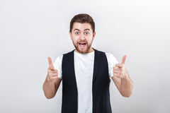 Portrait of handsome young smiling man in white shirt showing thumbs up gesture on gray background. Royalty Free Stock Photography