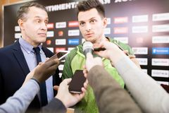 Reporters Interviewing Sportsman. Portrait of handsome young sportsman and his manager giving interview to group of journalists during press conference Stock Image