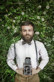 Portrait of handsome young in suit man with camera laing in green grass and ooking at camera. Man Camera Photographing Classic Ret Royalty Free Stock Photos