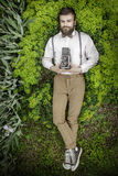 Portrait of handsome young in suit man with camera laing in green grass and ooking at camera. Man Camera Photographing Classic Ret Royalty Free Stock Images