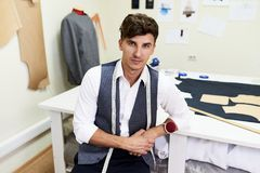 Handsome Fashion Designer Posing in Atelier Royalty Free Stock Photography