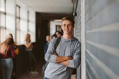 Student in high school campus. Portrait of handsome young university student standing and leaning to a wall in college corridor with other students at the back Stock Images