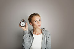 Portrait Handsome Young Woman Posing Blank Gray Background.Pretty Girl Smiling Holding Vintage Alarm Clock Hand Empty stock photography