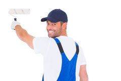 Portrait of handyman in overalls using paint roller Royalty Free Stock Photography
