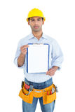 Portrait of a handyman in yellow hard hat holding a clipboard Stock Image