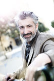 Portrait of a hansome man sitting outdoors. Handsome mature man walking in town Stock Image