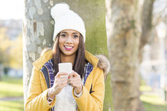Portrait of happiness woman with hat holding phone, outdoor. Stock Image