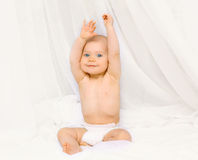 Portrait of happy active baby in diapers playing on the bed Royalty Free Stock Images
