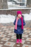 Portrait of happy adorable child laughing on city street during snowfall. Cute little caucasian girl in knitted hat and scarf and. Dawn jacket having fun stock images