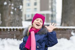 Portrait of happy adorable child laughing on city street during snowfall. Cute little caucasian girl in knitted hat and scarf and. Dawn jacket having fun stock image