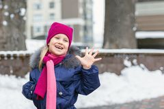Portrait of happy adorable child laughing on city street during snowfall. Cute little caucasian girl in knitted hat and scarf and. Dawn jacket having fun stock photos